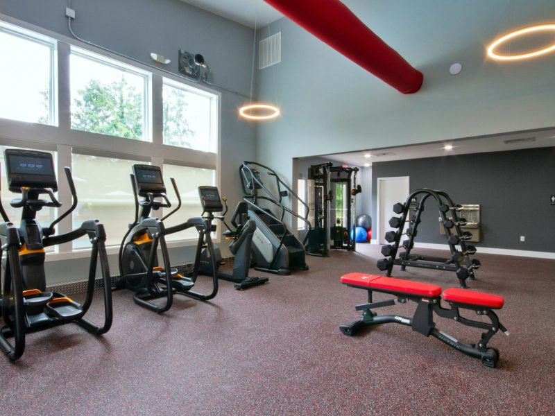 A picture showing the workout athletic club showing stair steppers, stationary bike, front of windows, a bench, and free weights and workout station with a drinking fountain on the wall.