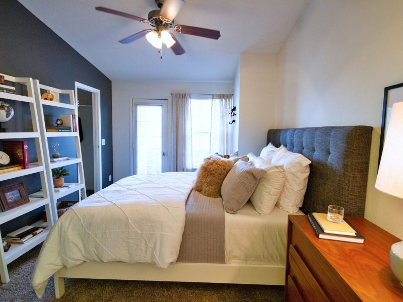 This image shows a master bedroom with modern lighting fixtures. It offers spacious floor plans, oversized windows with blinds, a huge shelf, and an ideal ceiling fan.