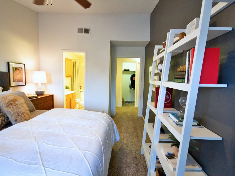 This image shows a master bedroom with direct access through the bathroom and closet. It offers spacious floor plans, oversized windows with blinds, a huge shelf, and an ideal ceiling fan.