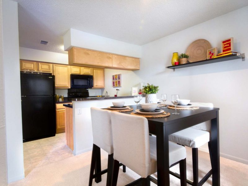 This image showcases the premium apartment feature, particularly the dining room featuring luxurious seats, elegant wall decor, and touch with modern ambiance. The Dining area has direct access through the kitchen island.