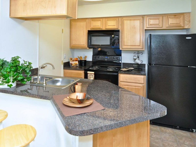This image shows fully equipped gourmet kitchens with high-end finishes and contemporary whirlpool appliances.
