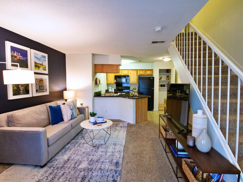 This image shows the premium apartment feature, particularly the living room area featuring a comfy sofa and vibrant wall sceneries. The living area is also featuring a stairway directing through the bedroom area.