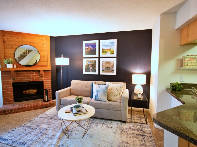 This image showcases the living room area featuring elegant wall scenery, comfy furniture, and an ideal wooden fireplace.