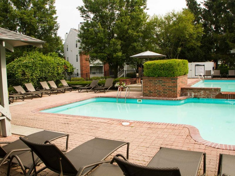 This image exhibits the comfy pool beds nearby the resort-style swimming pool in TGM Meadow View Apartments.