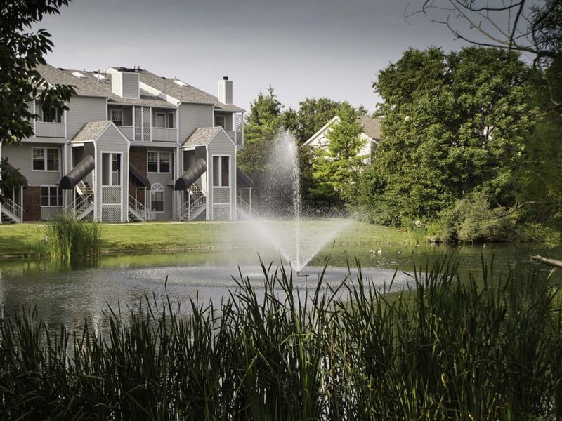 This image showcases the warm pond-side view of the TGM Meadow View Apartments. It features the glittering fountain and spectacular look of the apartments.